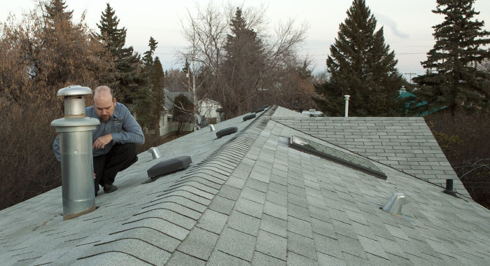 home inspector inspecting a roof in Camrose